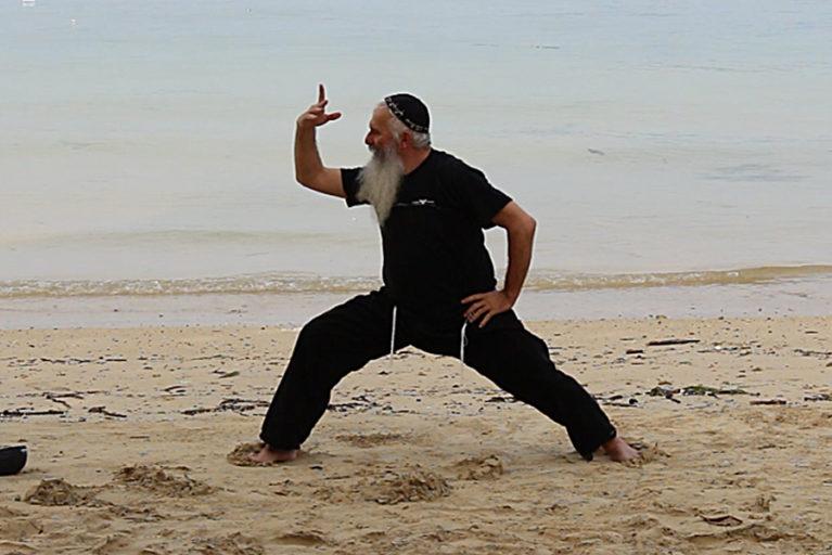 Mosche Kastiel zeigt Qi Gong übungen am Strand